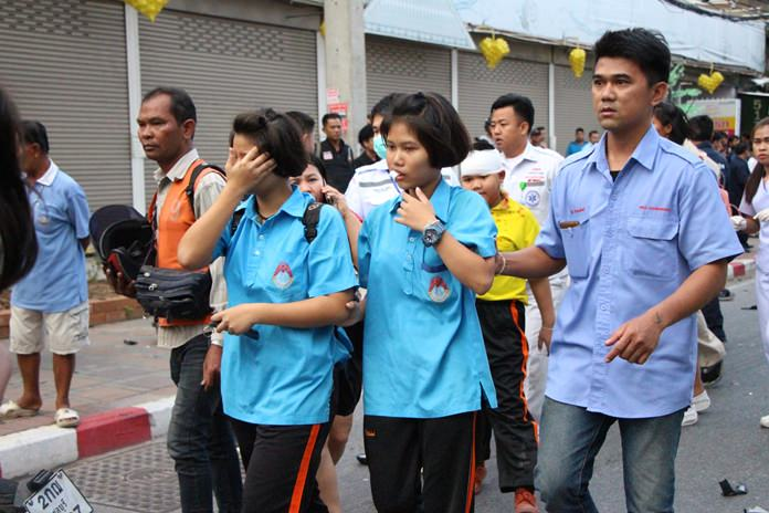Schoolgirls are led away from the scene by rescue workers.