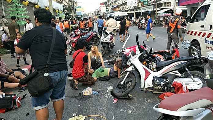 Motorbikes lie wrecked as passersby come to the aid of injured riders.