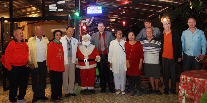 Rotarians and guests pose with Santa Claus at Prem's Christmas party.