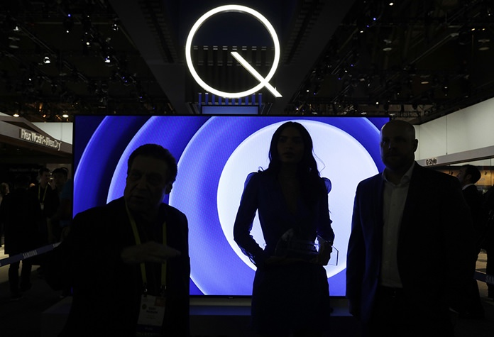 In this Friday, Jan. 6, 2017, file photo, attendees stand in front of a QLED TV at the Samsung booth during CES International in Las Vegas. (AP Photo/John Locher, File)