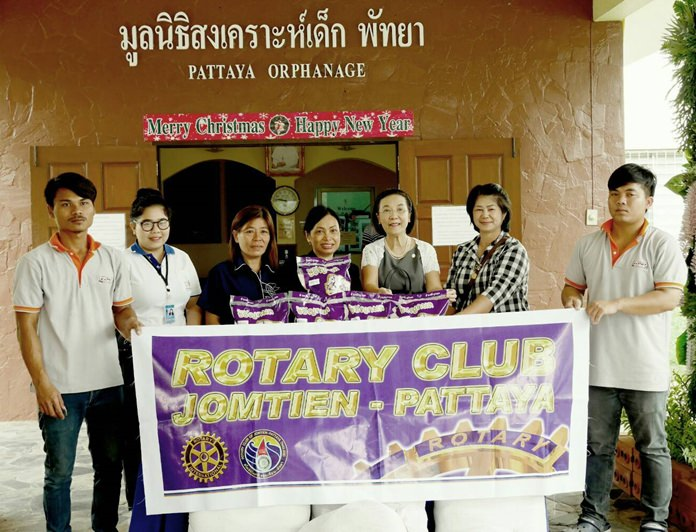 Radchada Chomjinda (3rd right) receives the rice on behalf of the Pattaya Orphanage from Nachlada Nammontree (center) and Ket Battaglino (3rd left).