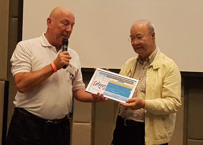 Mechai Viravaidya accepts the PCEC's Certificate of Appreciation from MC Roy Albiston.