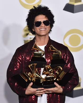 Bruno Mars poses in the press room with his awards at the 60th annual Grammy Awards ceremony in New York, Sunday, Jan. 28. (Photo by Charles Sykes/Invision/AP)