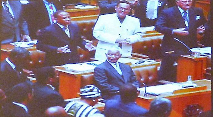 In this photo displayed during his presentation, H.E. Ambassador Geoff Doidge (white suit) stands behind a sitting Nelson Mandela during the time he was in Parliament and Nelson Mandela was President.
