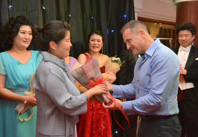 Zoltan Zakor, Vanichwathana Director presents a bouquet to cellist Yuscha Kim.