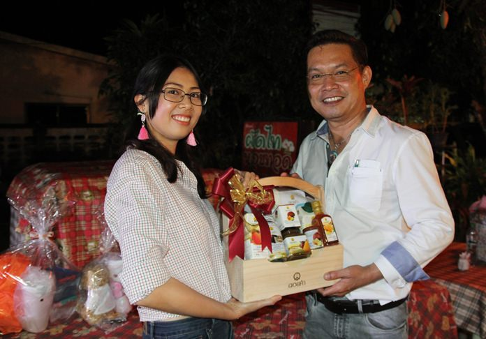 Nutsara Duangsri presents a gift to Peerasan 'Victor' Wongsri, director of Omthong Law & Auditing office.