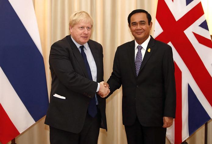 British Foreign Secretary Boris Johnson, left, shakes hands with Thai Prime Minister Prayuth Chan-Ocha during their meeting at the Government House, in Bangkok, Monday, Feb. 12. (Narong Sangnak/Pool Photo via AP)