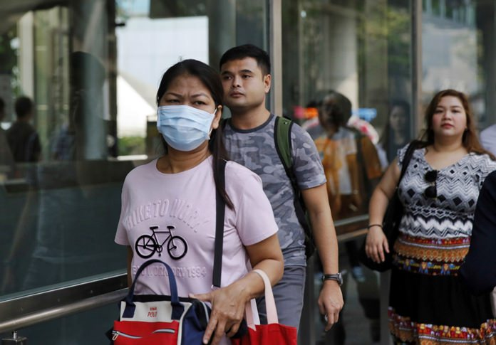 A woman wears a face mask to filter out some of the thick air pollution in downtown Bangkok. (AP Photo)
