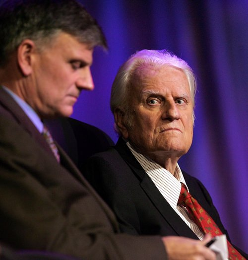 In this March 12, 2006 file photo, the Rev. Billy Graham, right, and his son Franklin Graham wait for the start of a service in New Orleans. (AP Photo/Bill Haber, File)