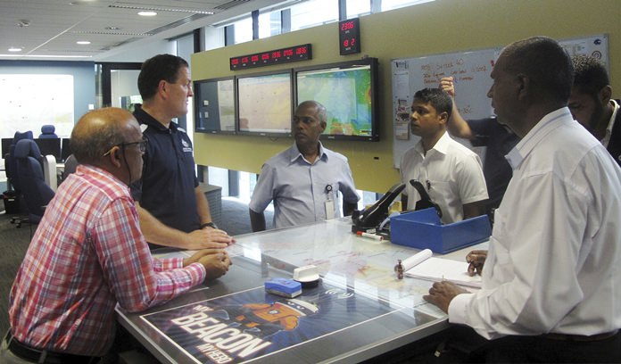 Australian search and rescue coordinator Rick Allen, second from left, trains foreign rescue officials in the Australian Maritime Safety Authority control room in Canberra, Australia. Officials from Mauritius, Maldives and Sri Lanka visited the authority's headquarters this week as part of a regional training program that began in 2015. (AP Photo/Rod McGuirk)