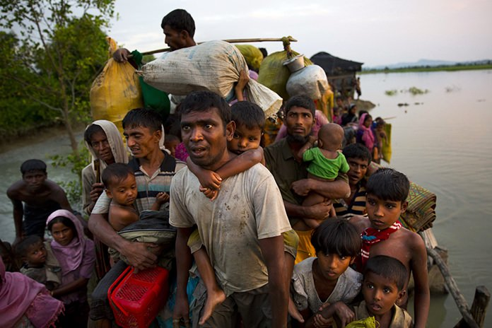 In this Nov. 1, 2017, file photo, Rohingya Muslims carry their young children and belongings after crossing the border from Myanmar into Bangladesh, near Palong Khali, Bangladesh. New satellite imagery of Myanmar's Rakhine state shows the country's government is using bulldozers to completely flatten dozens of Rohingya Muslim villages that were burned during violence last year. (AP Photo/Bernat Armangue, File)