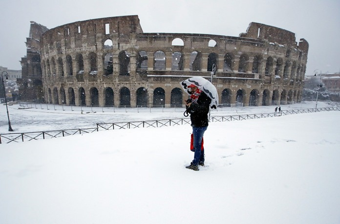 A man stands in front of the ancient Colosseum blanketed by the snow in Rome, Monday, Feb. 26. (AP Photo/Alessandra Tarantino)