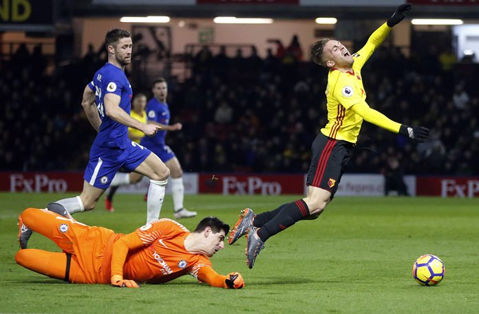 Chelsea goalkeeper Thibaut Courtois, left, fouls Watford's Gerard Deulofeu, right, during the English Premier League match between Watford and Chelsea at Vicarage Road stadium in Watford, Monday, Feb. 5. (AP Photo/Frank Augstein)