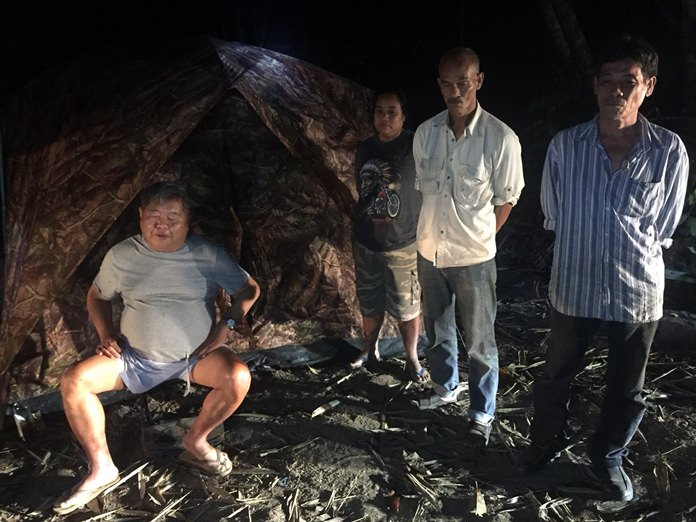 In this Feb. 4, 2018, photo, the president of Italian-Thai Development, Premchai Karnasuta, left, is seen with others in his group as they are detained in the Thungyai Naresuan Wildlife Sanctuary, in Kanchanburi province. (Thailand Department of National Parks, Wildlife and Plant Conservation via AP)