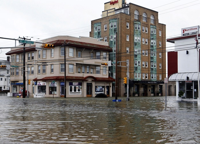 In this Oct. 30, 2012 file photo, the intersection of 8th Street and Atlantic Avenue is flooded in Ocean City, N.J., after the storm surge from Superstorm Sandy flooded much of the town. New satellite research shows that global warming is making seas rise at an ever increasing rate. (AP Photo/Mel Evans, File)