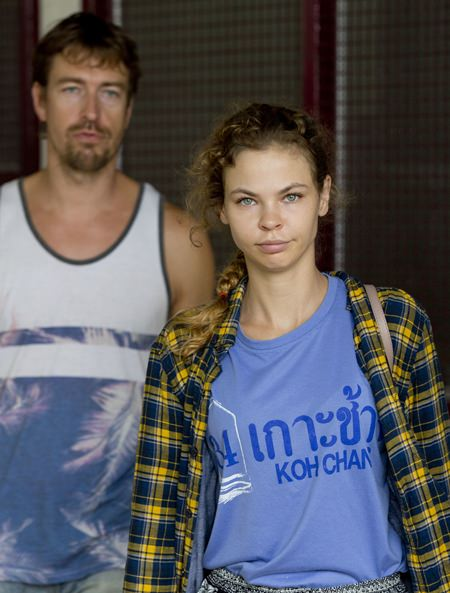 Anastasia Vashukevich, right, and Alexander Kirillov walk from a detention center in Pattaya, Wednesday, Feb. 28, 2018, after being arrested Sunday. Vashukevich told The Associated Press from a police van Wednesday that she fears for her life, and wants to exchange information on alleged Russian ties to U.S. President Donald Trump's campaign for her own personal safety. (AP Photo/Gemunu Amarasinghe)