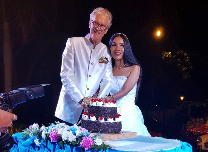 Jo and Noi cut the 'Schwarzwaelder Kirschtorte' wedding cake during the reception.