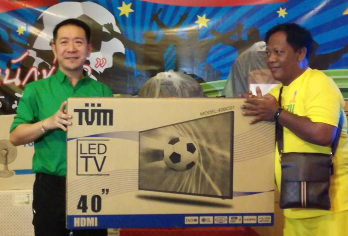 Banglamung District Chief Naris Niramaiwong was the guest of honor. Shown here, he presents the grand prize 40 inch LED TV to Tapanapong Siwilai from TMN.