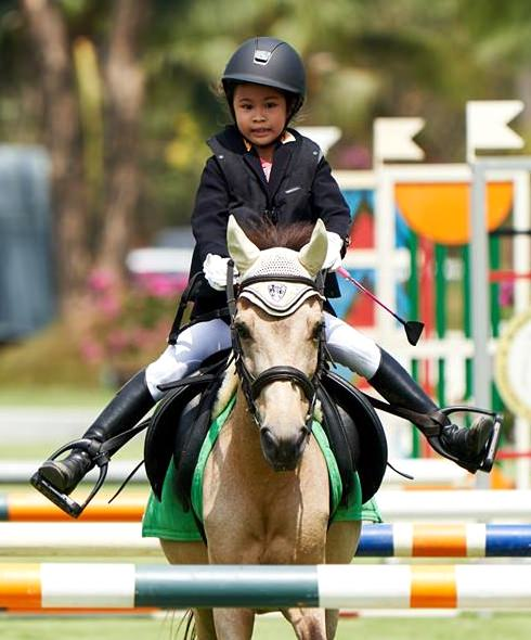 A young equestrian displays first rate horse-handling skills.