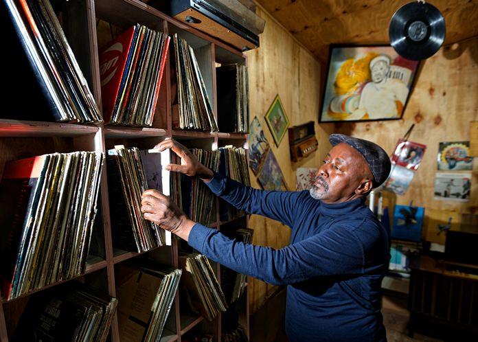 "In this photo taken Thursday, March 1, 2018, James ""Jimmy"" Rugami looks through records inside his vinyl records stall in Kenyatta Market in Nairobi, Kenya. (AP Photo/Ben Curtis)"