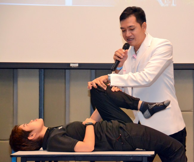 Nat with the aid of an assistant shows his audience how to perform certain exercises to treat their lower back pain.