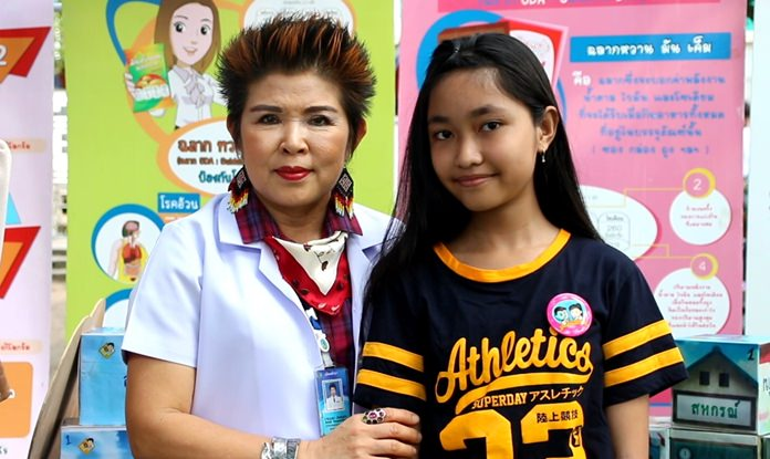 Pattaya Consumer Protection Office Director Buppa Songsakulchai awards a student with a healthy pin upon completion of the Little Food and Drug Project.