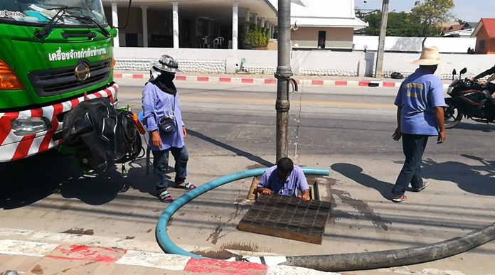 Pattaya sanitation workers clean out drains along Beach Road to mitigate flooding.
