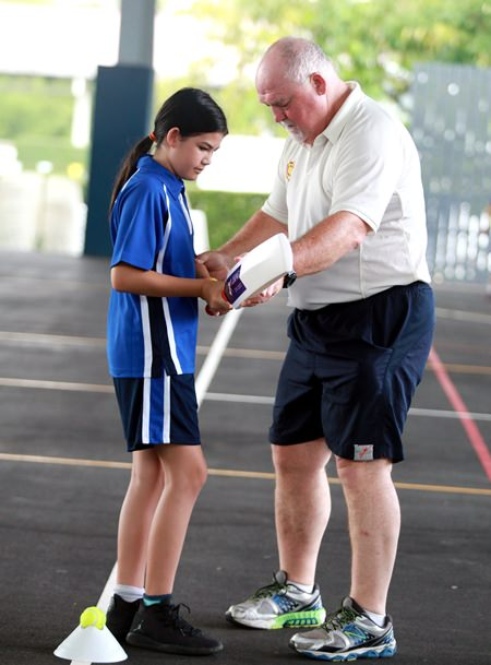 Cricket star Mike Gatting (right) gives batting tips to a GIS student.