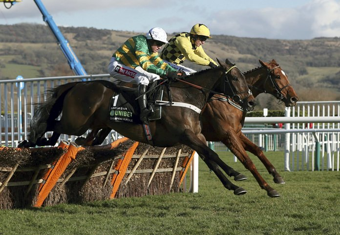 Race winner Buveur D'Air ridden by Barry Geraghty, foreground, clears the last hurdle alongside Melon, ridden by Paul Townend, as they race to finish-line in the Champion Hurdle at Cheltenham Racecourse, Cheltenham England Tuesday March 13. (David Davies/PA via AP)
