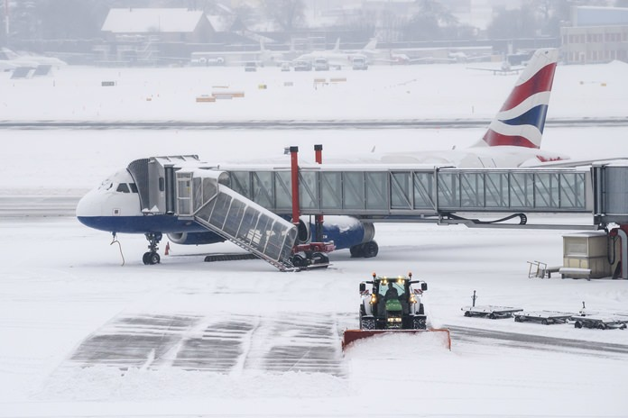 The fire brigade of Airport Security Services (SSA) ride a snowplow removing snow on the runway at the Geneva Airport, in Geneva, Switzerland, Thursday, March 1. (Martial Trezzini/Keystone via AP)