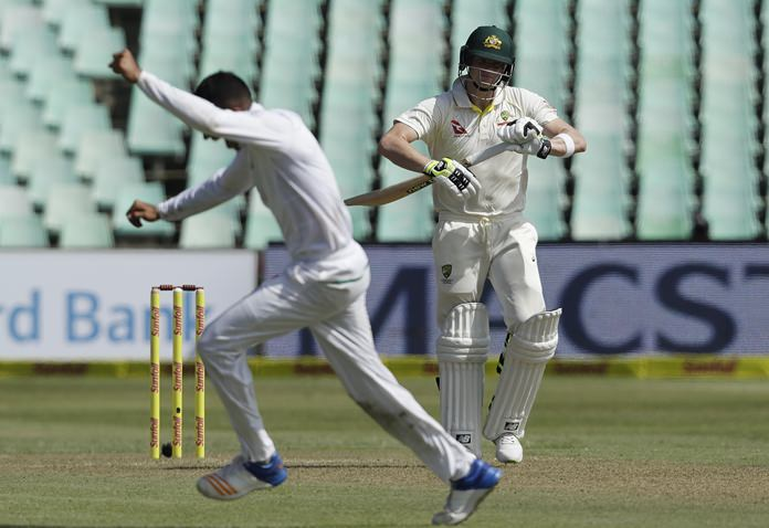 Australia's captain Steven Smith, right, watches as South Africa's bowler Keshav Maharaj' celebrates his dismissal for 56 runs on day one of the first test match between South Africa and Australia at Kingsmead stadium in Durban, South Africa, Thursday, March 1. (AP Photo/Themba Hadebe)