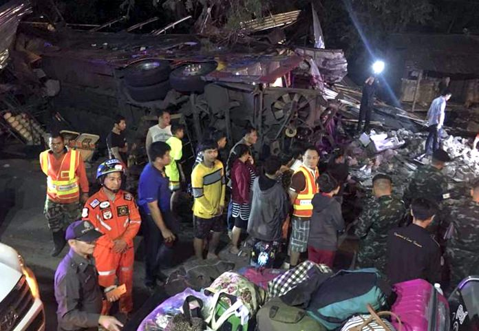 A mangled bus lies on its side as people look through debris scattered nearby Wednesday night, March 21, in Nakhon Ratchasima province. (Daily News via AP)