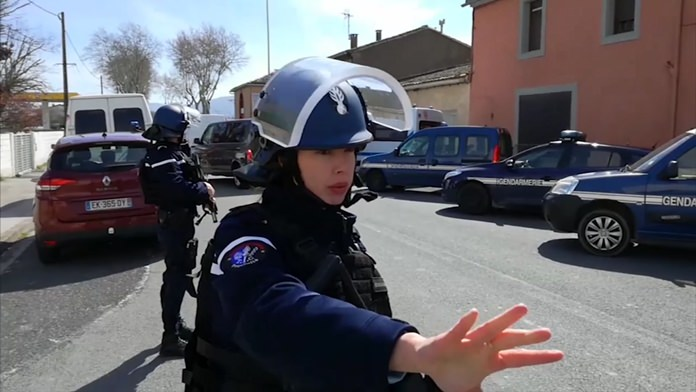 Police officers attend a shooting and hostage taking incident in Trebes, southern France, Friday March 23. (La Depeche Du Midi via AP)