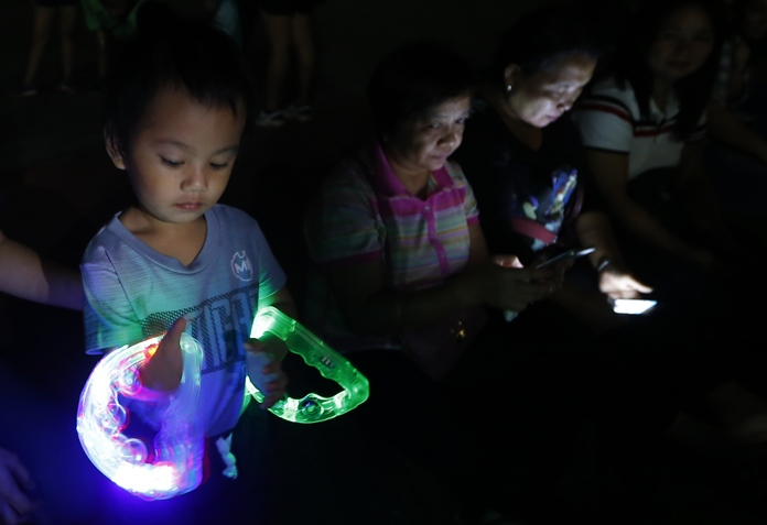 A Filipino girl plays with a light toy in observance of Earth Hour, a global event that raises awareness on the need to take action on climate change Saturday, March 24, in suburban Pasay city southeast of Manila. (AP Photo/Bullit Marquez)