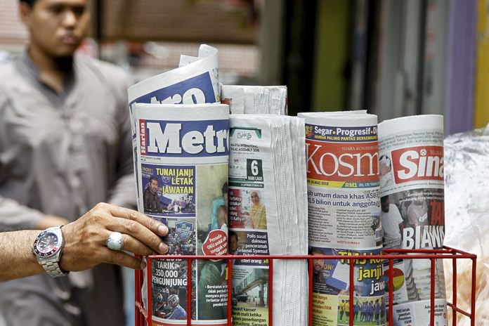 A man takes a copy of newspaper at a grocery shop in Shah Alam, Malaysia, Monday, March 26. (AP Photo/Sadiq Asyraf)