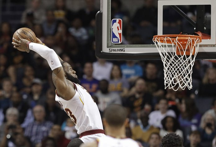 Cleveland Cavaliers' LeBron James goes up to dunk against the Charlotte Hornets during the first half of an NBA basketball game in Charlotte, N.C., Wednesday, March 28. (AP Photo/Chuck Burton)
