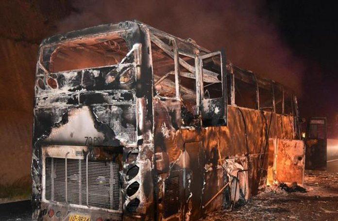 A burnt double-decker bus is seen in Tak province, Thailand, Friday, March 30. (Daily News via AP)