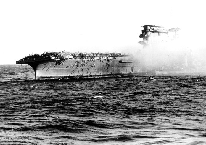 In this 1942 file photo, the crew abandons the USS Lexington after the aircraft carrier was critically damaged in the Battle of the Coral Sea during World War II. (U.S. Navy via AP)
