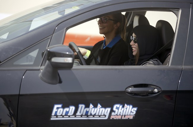 Fatima Salem, right, giggles as she sits for the first time in the driver's seat, with her trainer Francesca Pardini, an Italian ex-race car driver, during training sponsored by Ford Motor, in Jiddah, Saudi Arabia, Tuesday, March 6. (AP Photo/Amr Nabil)