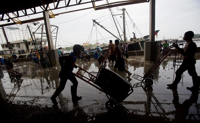 In this June 20, 2014, file photo, migrant workers unload frozen fish from a boat at a fish market in Samut Sakhon Province, west of Bangkok. (AP Photo/Sakchai Lalit)