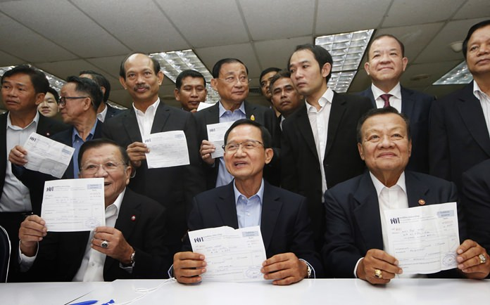 Thailand's former Prime Minister Somchai Wongsawat, front center, and former lawmakers show receipts after registering their memberships to the Pheu Thai Party in Bangkok, Wednesday, April 4. (AP Photo/Sakchai Lalit)