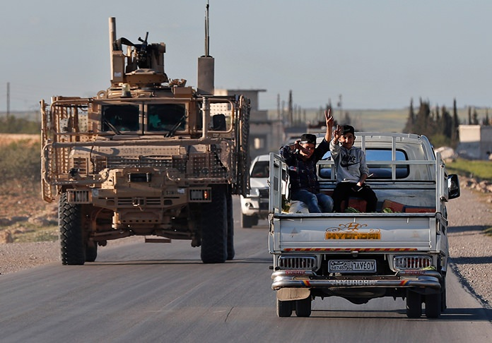 """In this Saturday, March 31, 2018 file photo, Syrian boys, right, sit on a pickup truck as they travel next to a U.S. vehicle, on a road leading to the tense front line with Turkish-backed fighters, in Manbij, north Syria. President Donald Trump expects to decide """"very quickly"""" whether to remove U.S. troops from war-torn Syria, saying their primary mission was to defeat the Islamic State group and """"we've almost completed that task."""" (AP Photo/Hussein Malla, File)"""