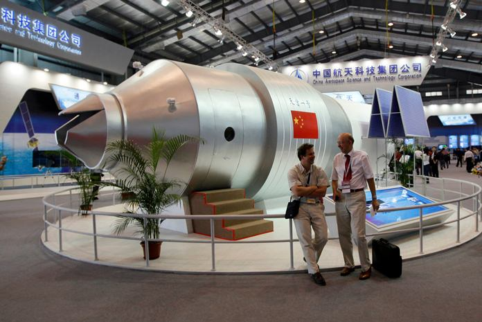 In this Nov. 16, 2010 file photo, visitors sit beside a model of China's Tiangong-1 space station at the 8th China International Aviation and Aerospace Exhibition in Zhuhai in southern China's Guangdong Province. (AP Photo/Kin Cheung, File)