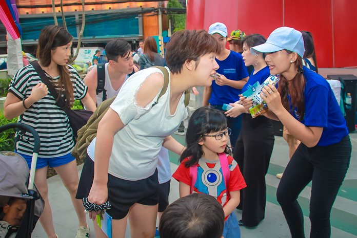 """Staffers from the Chonburi Tourist Assistance Center hand out """"Do's and Don'ts Guidelines for Tourists"""" booklets in Pattaya."""