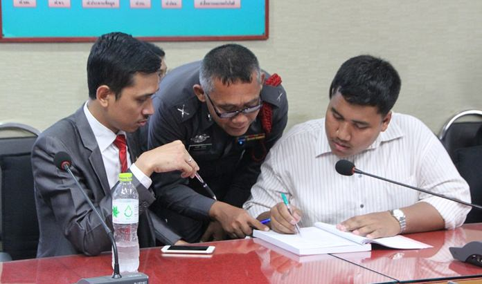 """Sirawit """"Ja New"""" Seritiwat (right) fills out pre-court date paperwork after organizing a pro-democracy rally in Pattaya last month."""