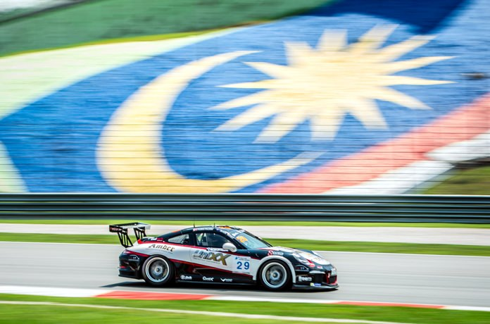The Unixx TR-Motorsport Racing team Porsche 911 negotiates a corner at the Sepang Circuit.