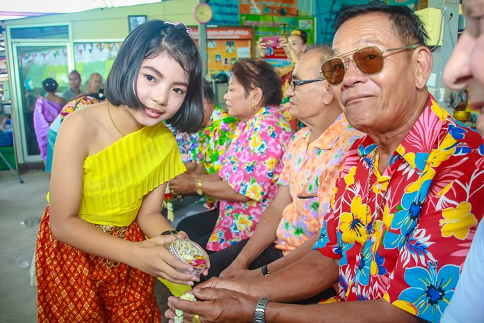 This young future movie star takes part in a traditional lustral water pouring ceremony, receiving blessings from the elders in the Soi Khopai community.