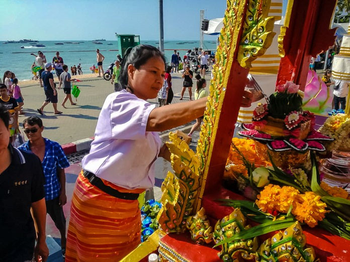 Residents and tourists pour lustral water on the Buddha relics when the parade reached their area.