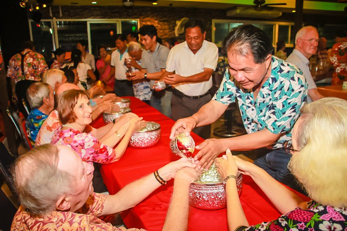 Members of the Rotary Club of Plutaluang join in the 'Rod Nam Dum Hua' ceremony.