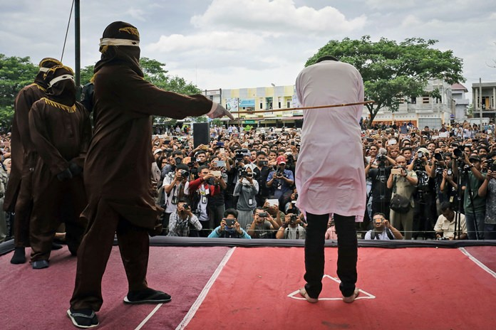 In this Tuesday, May 23, 2017 file photo, a Shariah law official whips a man convicted of gay sex during a public caning outside a mosque in Banda Aceh, Aceh province Indonesia. (AP Photo/Heri Juanda)